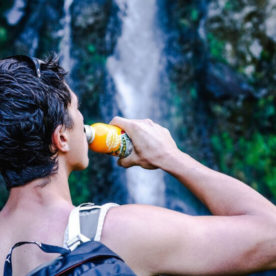 Backpacker drinking a bottle of Buriti flavored juice while facing a waterfall