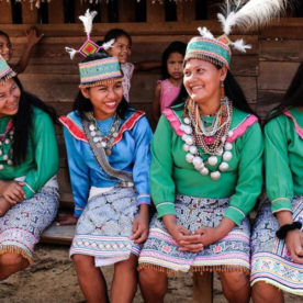 Four women from an indigenous community sitting on a bench